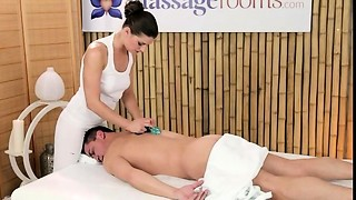 Masseur rubs dick with knockers and feet on massage table